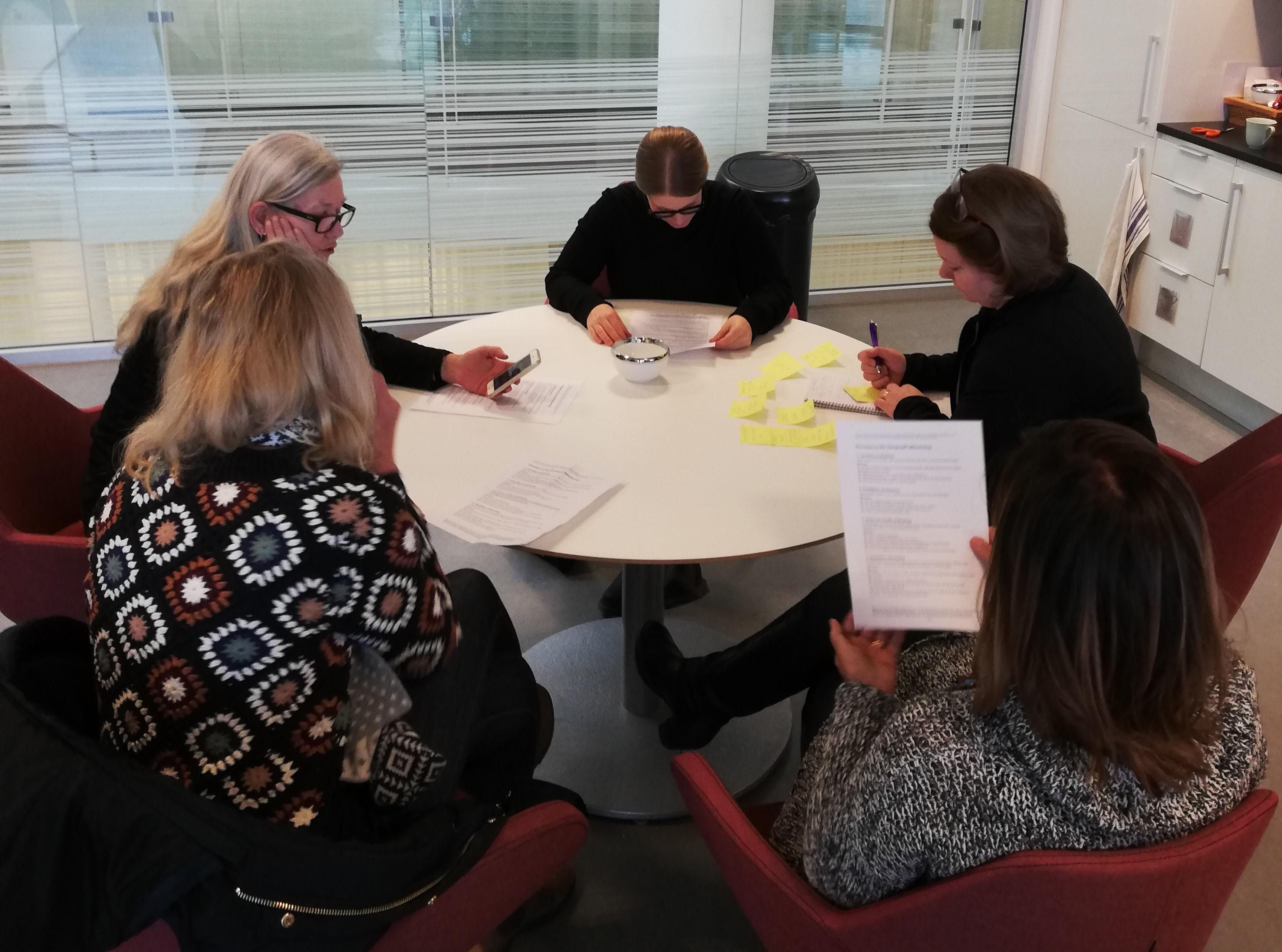 Bilden visar fem personer runt ett bord som läser och gör en gemensam uppgift