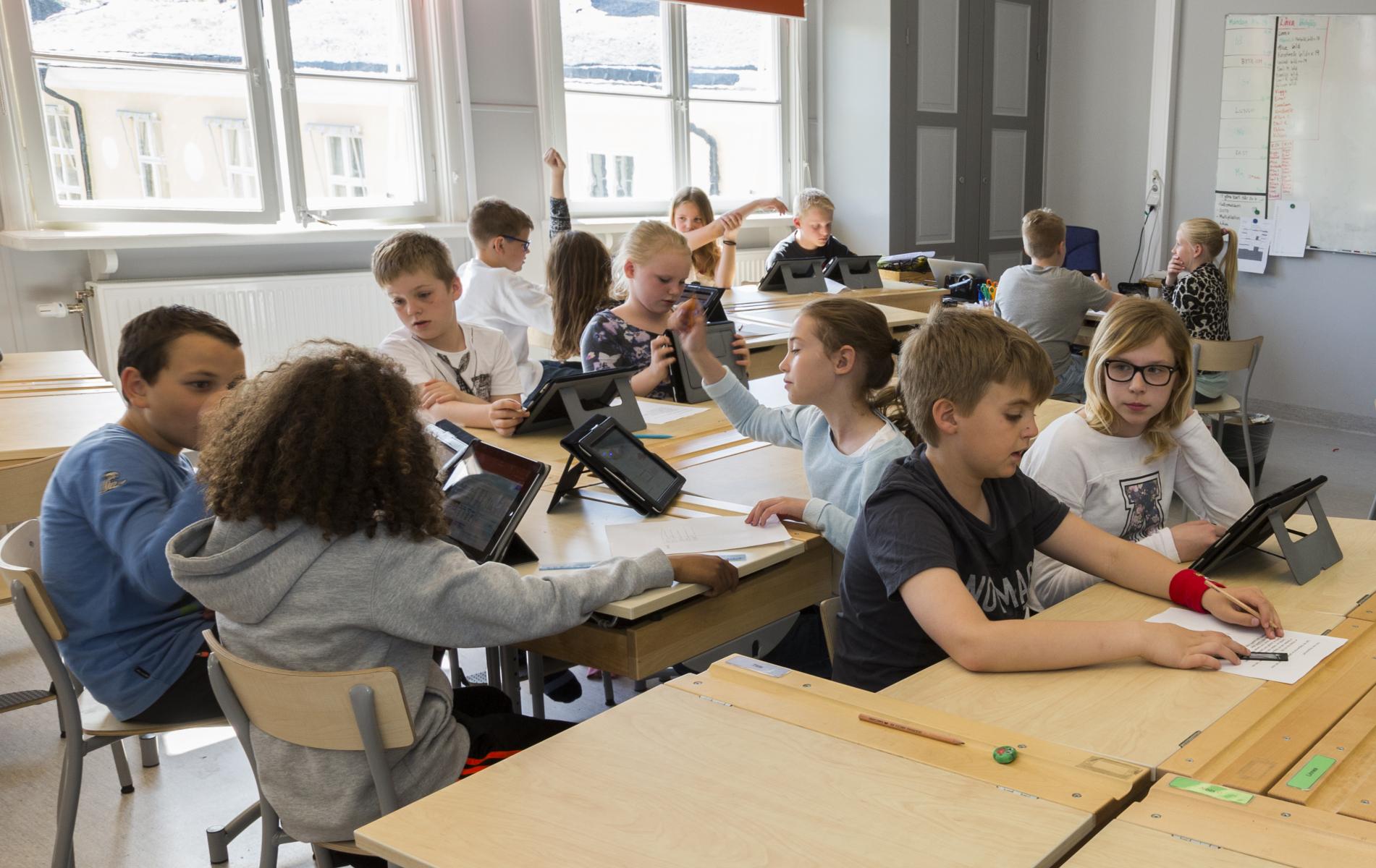 Barn i ett klassrum som använder läsplattor
