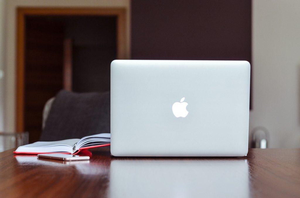 Bilden visar en laptop med uppfälld skärm på ett bord. Det finns en uppslagen bok och en mobiltelefon vid sidan av datorn.