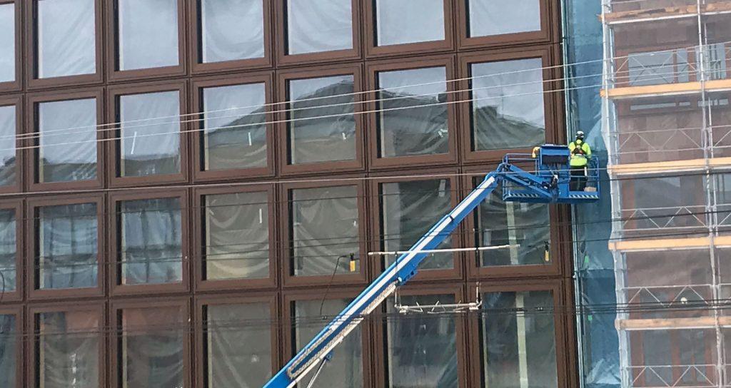 Bilden visar ett pågående bygge av ett stort hus med glasfönster och en byggarbetare på en kran. I fönsterrutorna speglas ett bostadshus.
