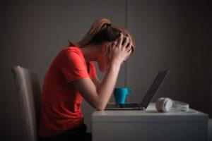En person sitter med nedböjt huvud vid skrivbordet , med en laptop framför sig