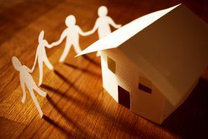 Pappersfigurer dansar hand i hand runt ett pappershus.